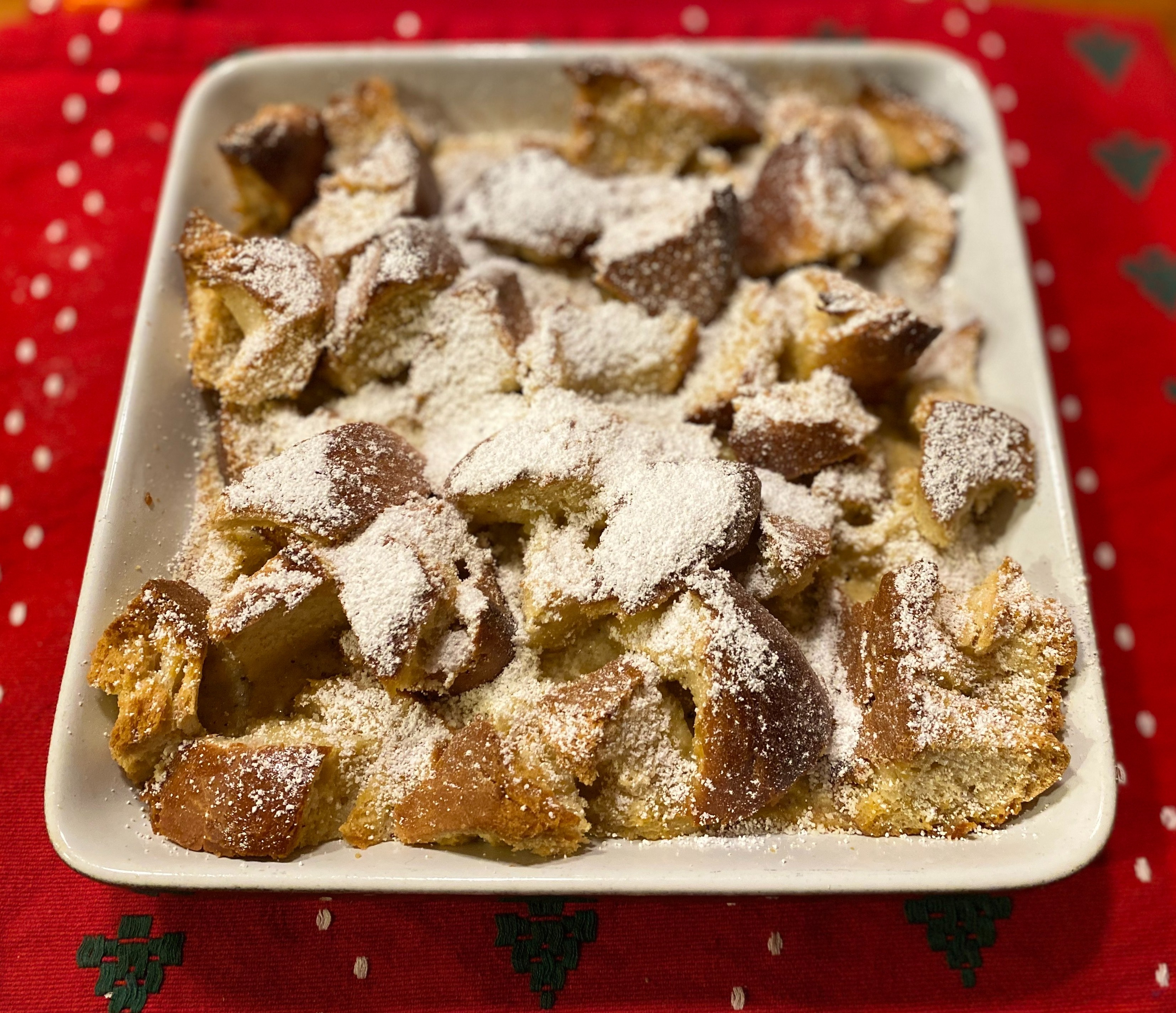 A simple bread pudding recipe with powdered sugar sprinkled on top.