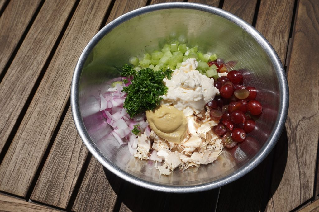 Add all your ingredients for chicken salad to a bowl before mixing together.