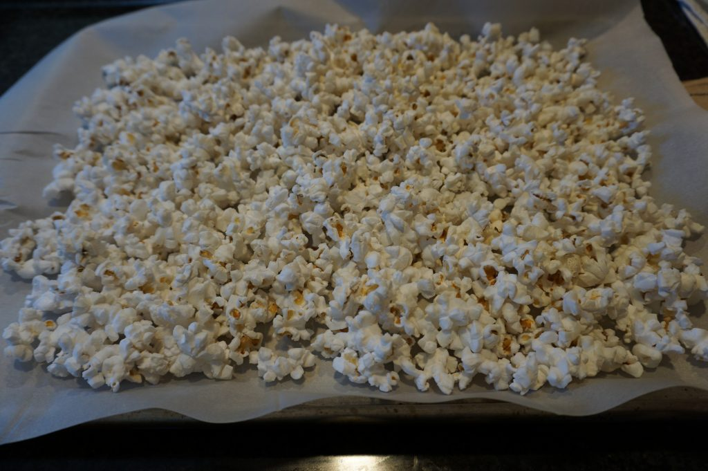 Spread popcorn out on wax or parchment paper